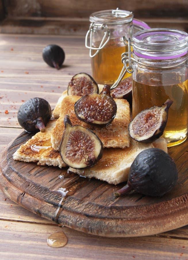 Tranches de pain grillé avec les figues et le miel photos stock