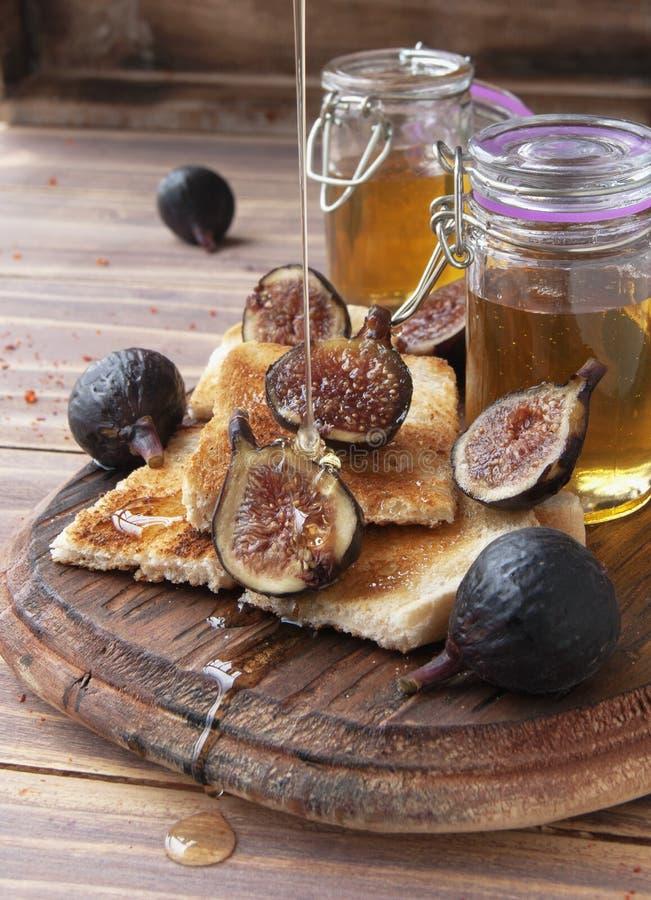 Tranches de pain grillé avec les figues et le miel photographie stock