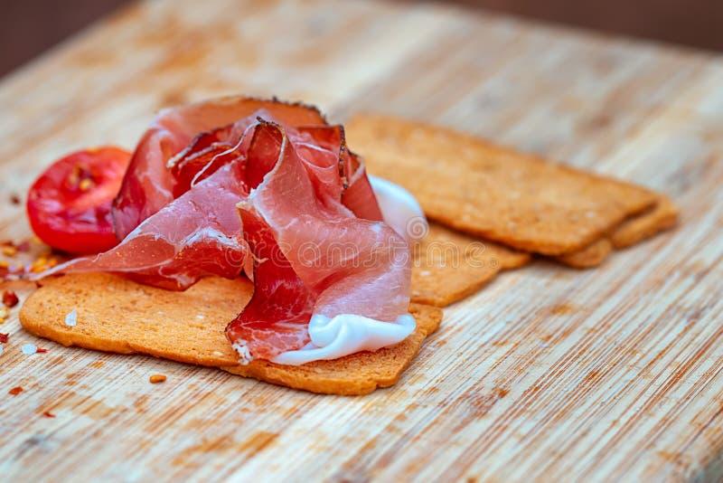 Tranches de pain sec avec du jambon et des tomates sur le conseil en bois photographie stock libre de droits