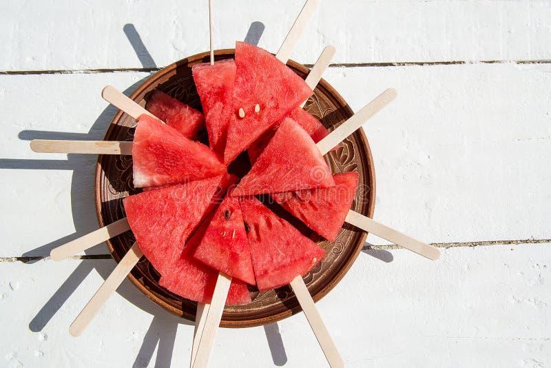 Tranches de pastèque mûre et juteuse d'un plat brun, se tenant sur a photographie stock libre de droits