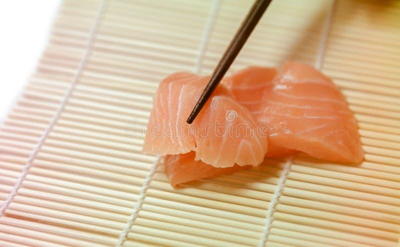 Tranches de sashimi saisies avec le plan rapproché de baguettes photo stock