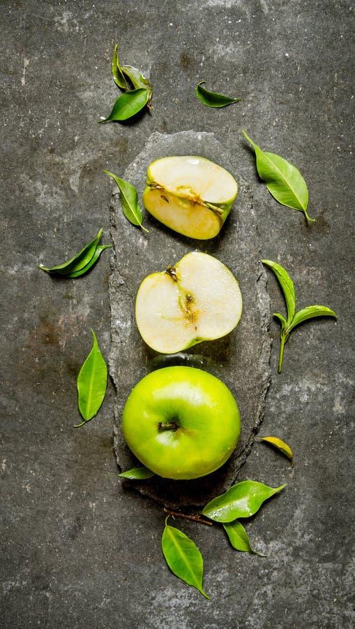 Tranches entières et coupées d'Apple vert avec des feuilles images stock
