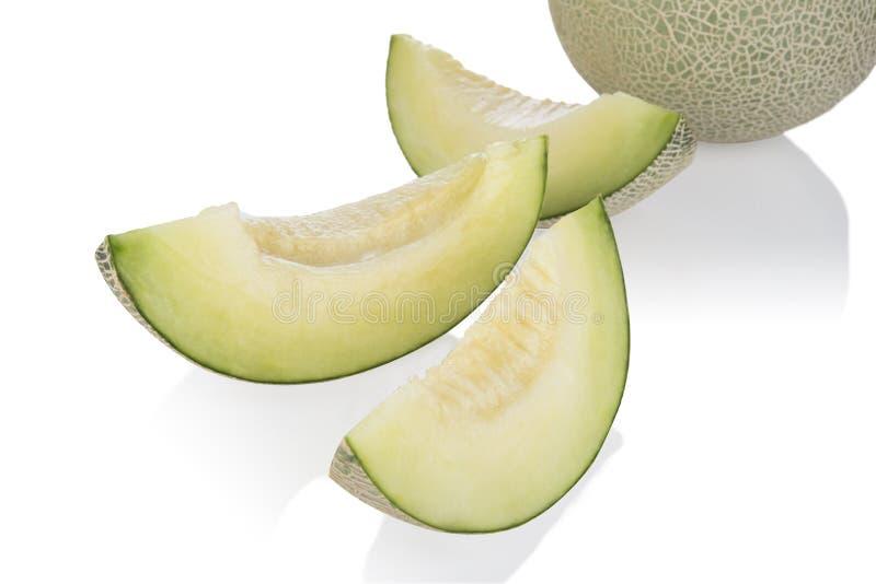 Tranches et moitié de melon de cantaloup d'isolement sur le fond blanc Avec le chemin de coupure image libre de droits