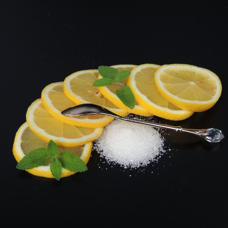 Tranches et sucre de citron sur un fond noir photographie stock libre de droits