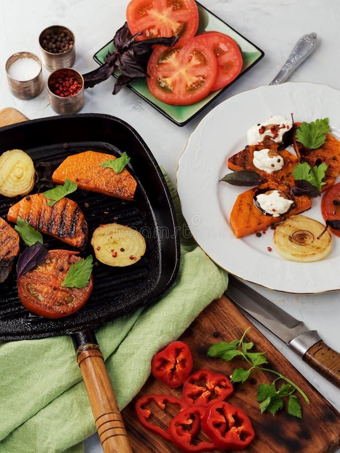 Tranches frites de potiron, oignons et saucisses sur une plaque blanche et poêle à friture en fonte noire Sauce crémeuse et balsa photos stock