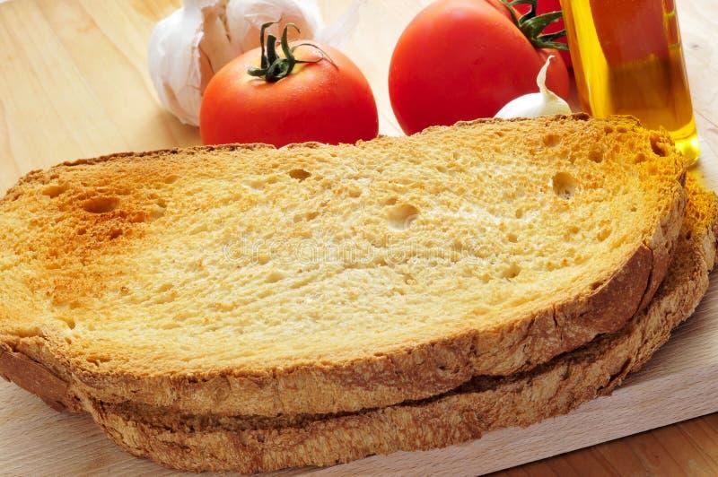 Tranches grillées de pain, et ail, huile d'olive et tomate images libres de droits