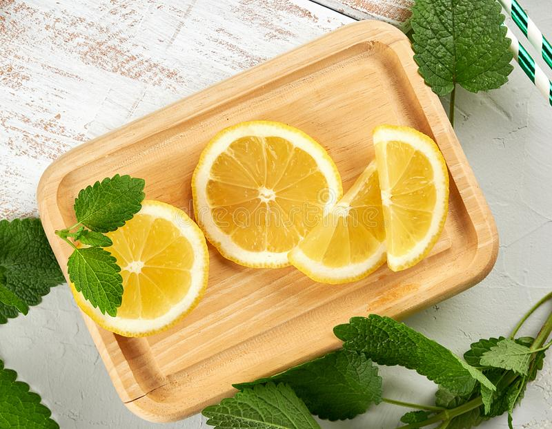 tranches juteuses jaunes découpées en tranches de citron et feuilles en bon état fraîches vertes image stock