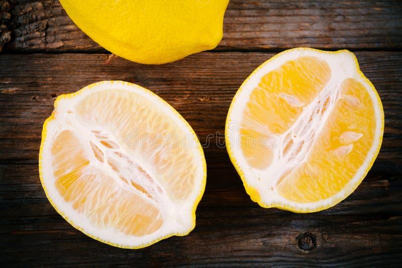 Tranches mûres fraîches de citron sur le fond en bois images stock