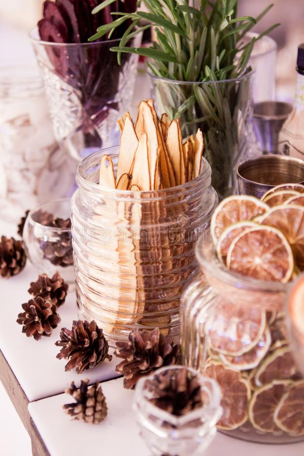 Tranches minces de betterave orange sèche de citron de poire Sur la table, pots en verre avec les fruits secs près des cônes de m image libre de droits