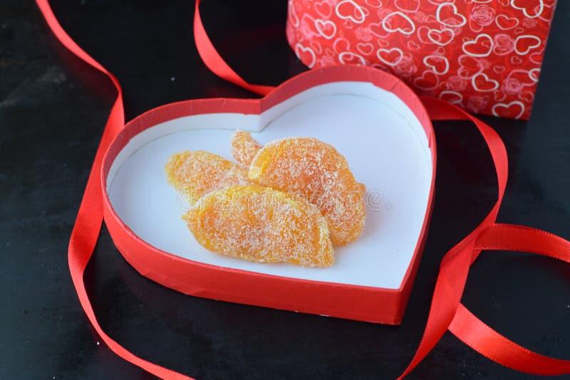 Tranches oranges glacées dans un couvercle rouge en forme de coeur d'une boîte avec le ruban rouge sur un fond noir Jour du ` s d image libre de droits