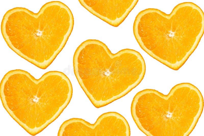 Tranches oranges sous forme de coeur sur un fond blanc pur image stock