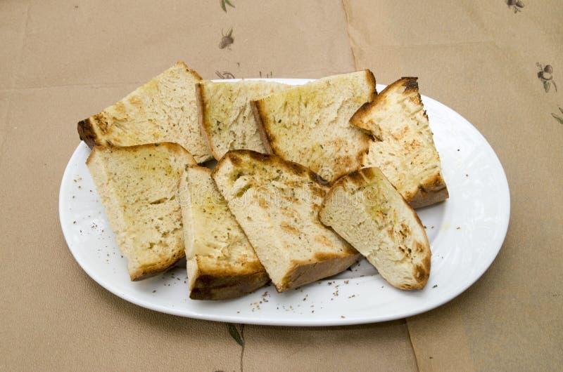 Tranches rôties de pain fait maison avec l'huile d'olive dans le plat en Grèce photo libre de droits
