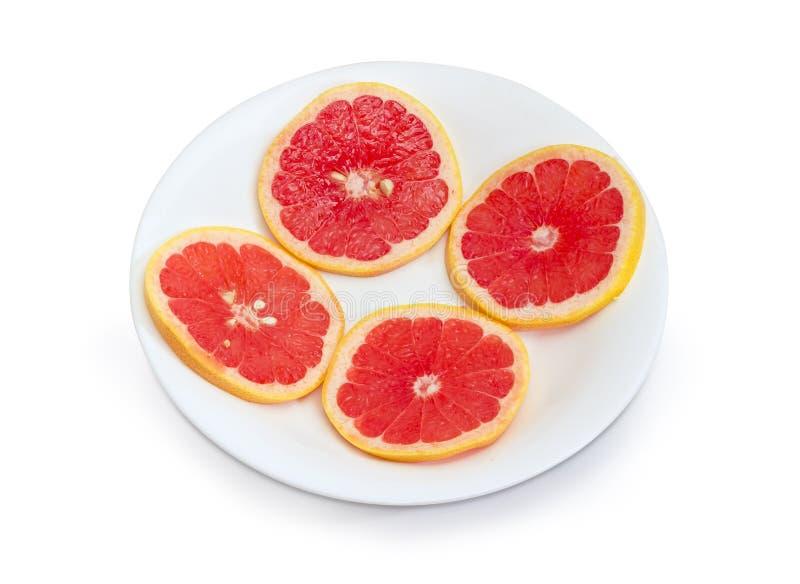 Tranches rondes du pamplemousse rouge sur un plat blanc photographie stock libre de droits