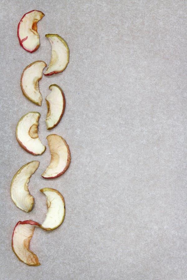 Tranches sèches de pomme sur le papier image stock