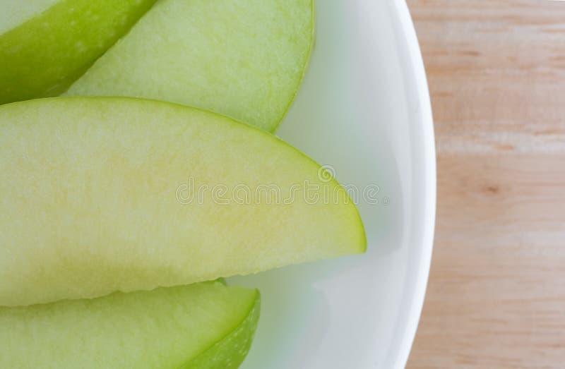 Tranches vertes de pomme sur une fin de dessus de table de plat photo stock
