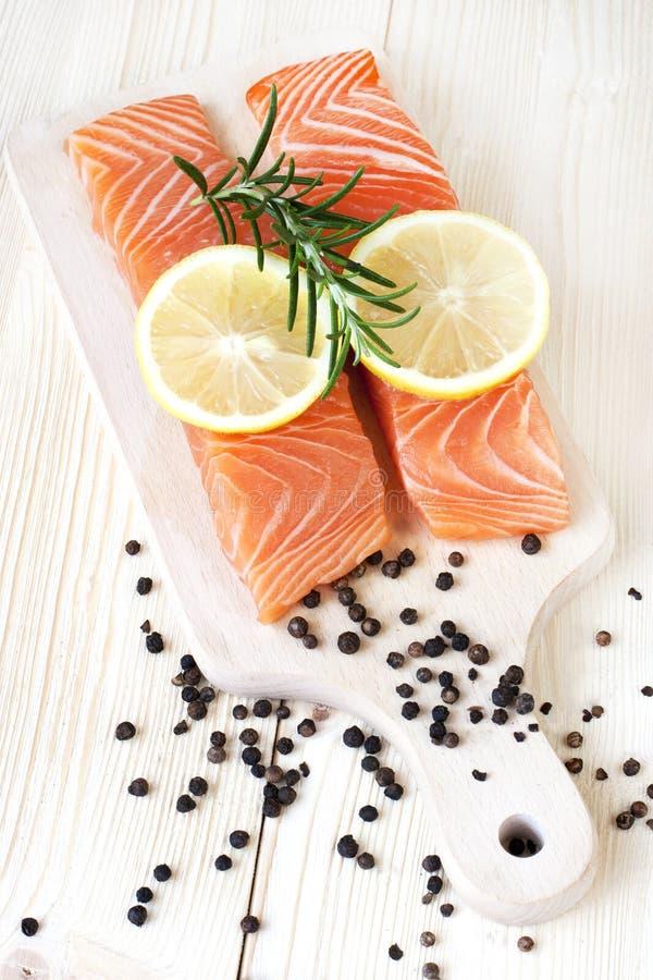 Tranci di pesce di color salmone crudi con le erbe fresche sul tagliere fotografia stock