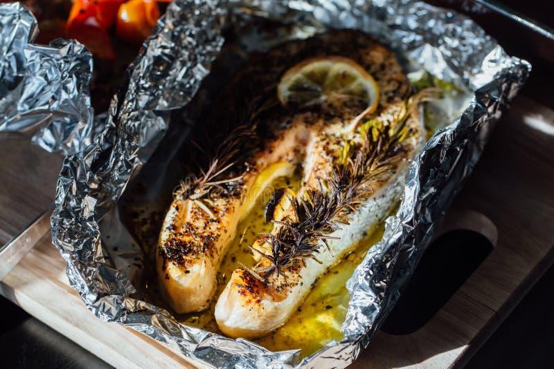 Trancio di pesce al forno con il limone e le erbe in stagnola fotografia stock