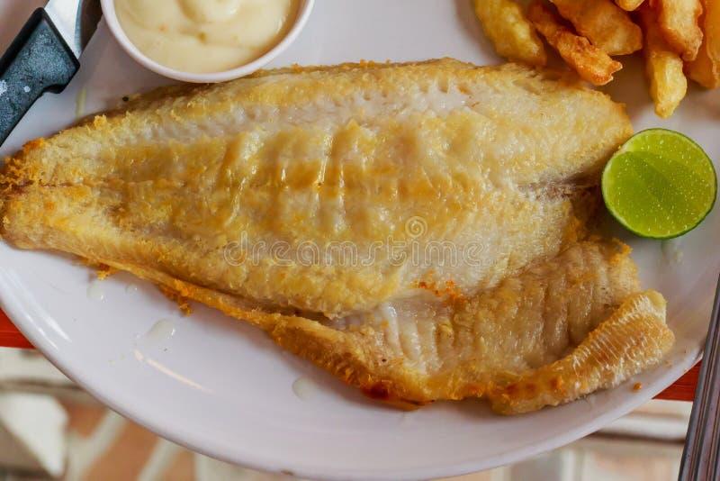 Trancio di pesce di tilapia su un piatto bianco immagini stock