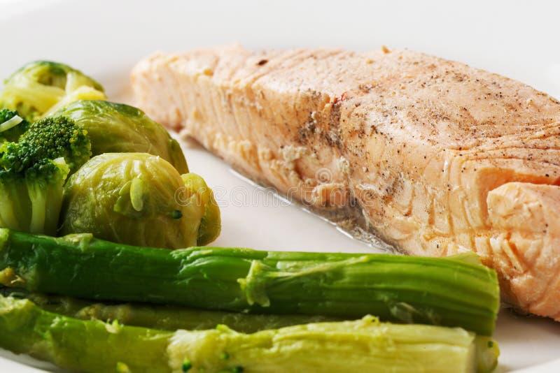 Trancio di pesce rosso arrostito con i cavolini di Bruxelles ed asparago in un piatto su un fondo bianco isolato immagini stock