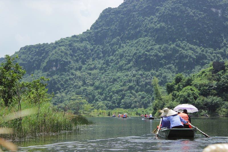 Trang, Ninh Binh, Vietnam - September 13,2014: De bezoekers bezoeken mooie rivier en berg van de boot langs de rivier stock afbeeldingen