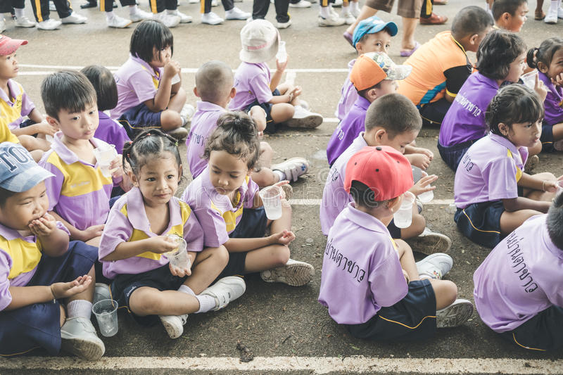 Trang, Thailand - June 23, 2017: Kindergarten children waiting for enjoy activity on sports day at public ground in Trang Thailand. Trang, Thailand - June 23 stock photo
