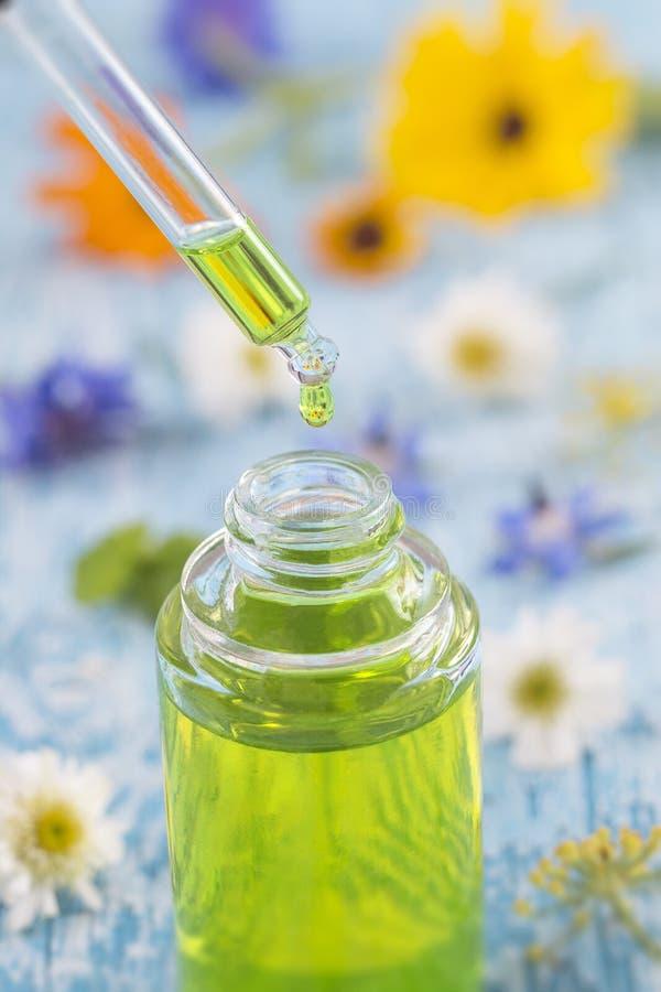 Tranparent glasflaskor med nödvändig flytande för droppar i droppglass på träbakgrund med medicinska blommor royaltyfri fotografi