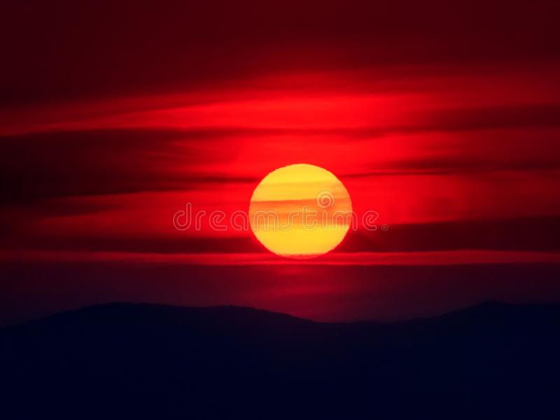 Tranquil autumn sun is rising from behind mountains, in a cold day with cloudy sky. Red perfect sun is lighting the sky with fire stock photos