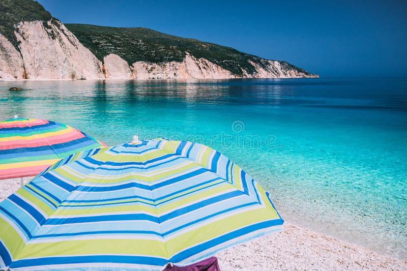 Tranquil beach scene. Picturesque landscape of mediterranean island with colorful umbrellas. Summer vacation holiday concept stock images