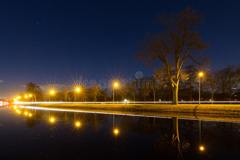 Tranquil canal perspective. Beautiful tranquil nightscape with car lights reflected in the canal at night with streetlights and a tree stock images