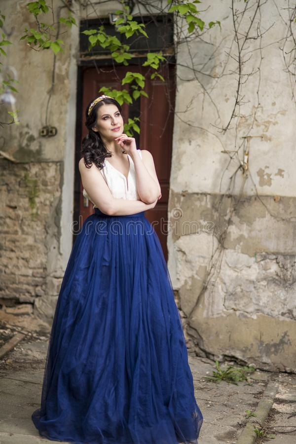 Tranquil Caucasian Lady in Long Blue Dress and Tiara Posing in Authentic Yard Outdoors. Vertical Shot stock photography