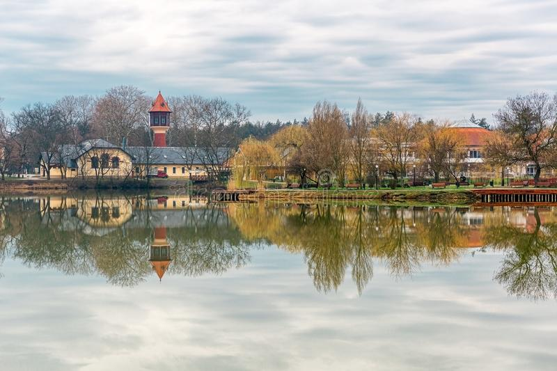 Tranquil landscape with lake, houses, cloudy sky, and trees reflected symmetrically in the water. Nyiregyhaza, Hungary royalty free stock photos
