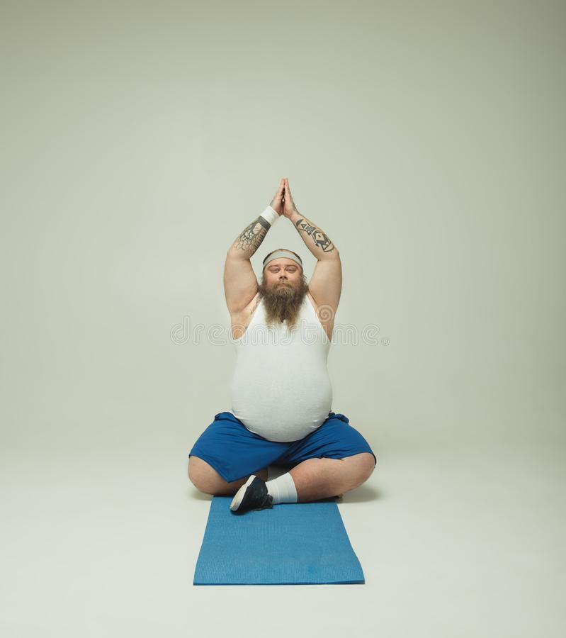 Tranquil male doing meditation on mat stock image