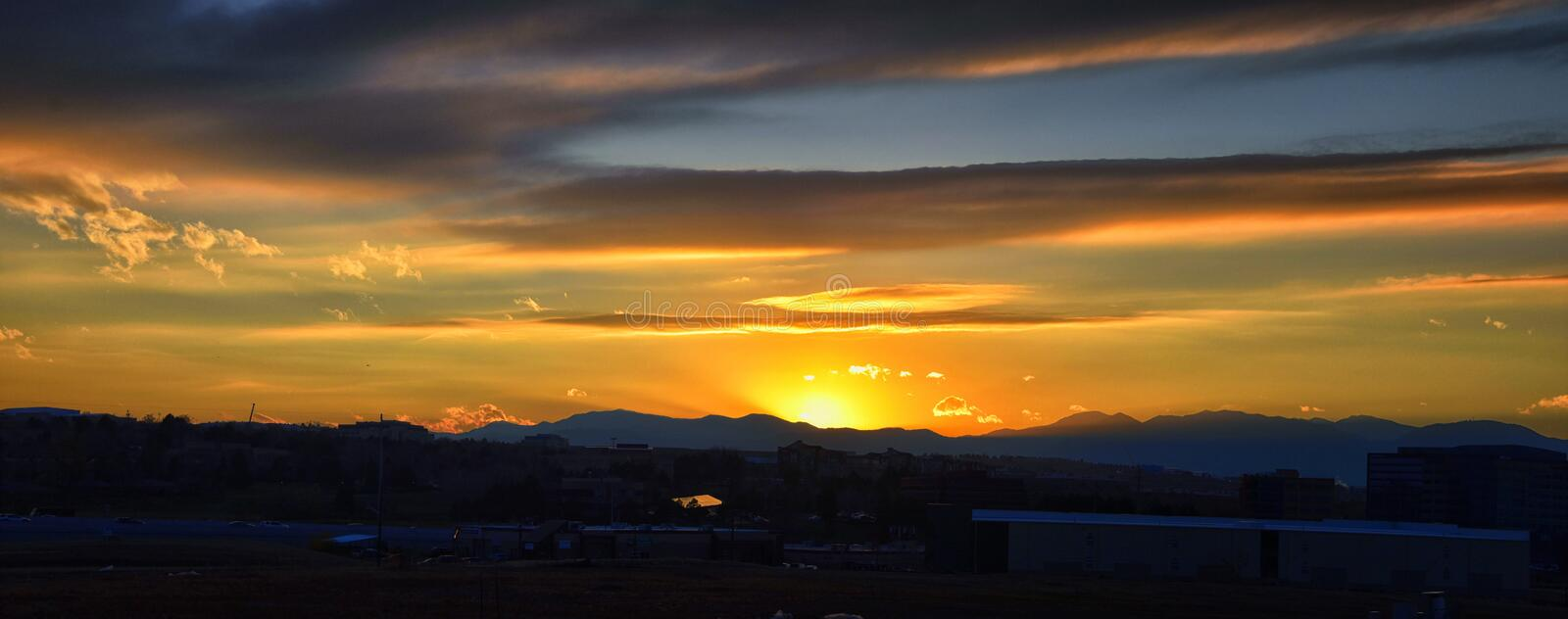 Tranquil panoramia scene of red sun and orange sky sunset over the Rocky Mountains in Colorado by Denver. United States stock photo