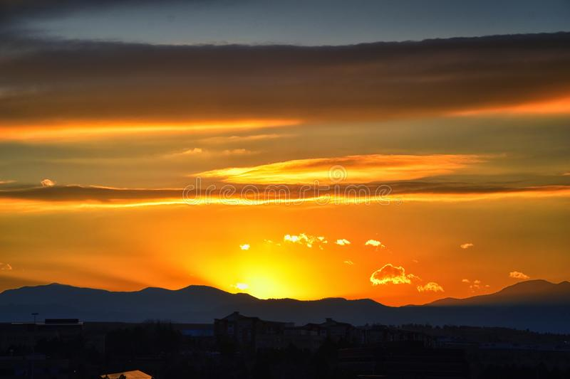 Tranquil panoramia scene of red sun and orange sky sunset over the Rocky Mountains in Colorado by Denver. United States stock images