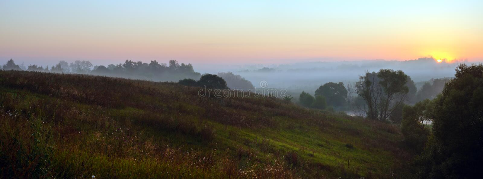 Tranquil panoramic landscape with trees and hills covered by morning fog. Beautiful panorama of foggy hills on a background of rising sun royalty free stock photography