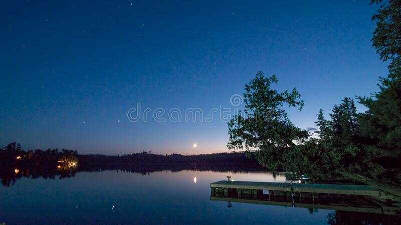 Tranquil peaceful late sunset - early evening on Hungry Jack Lake with dock / pier, moon, stars, and cabins off the Gunflint Trail. In Northern Minnesota stock images