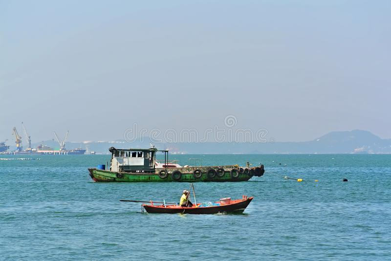 Scenery of Small Colorful Boat In Front of Green Fisherman Boat in the Sea stock photos