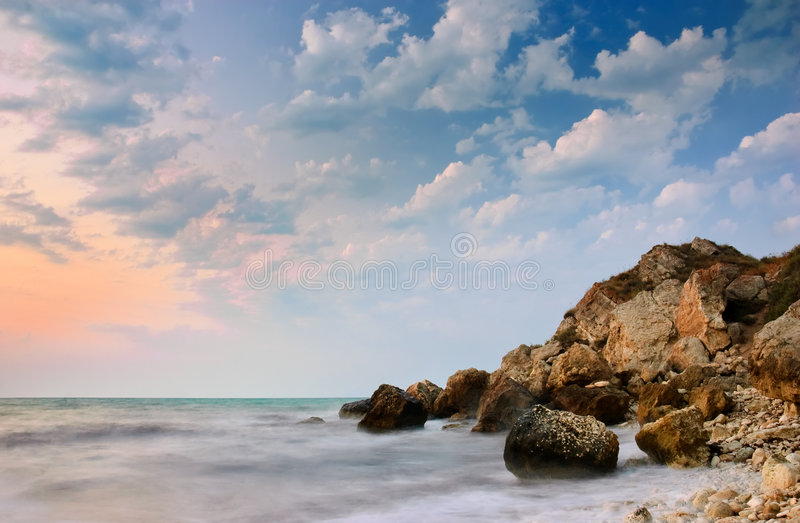 Tranquil sea after sunset. Vanilla sky and motion blur on the water stock images