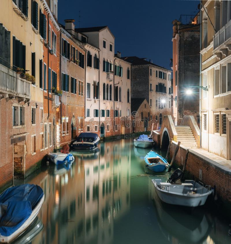 Tranquil canal with colorful buildings and boats at night, Venice, Italy. Tranquil street view with colorful buildings along canal and boats at night, Venice stock image