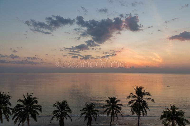 Tranquil sunrise in Hua Hin beach with coconut trees, Thailand stock photo