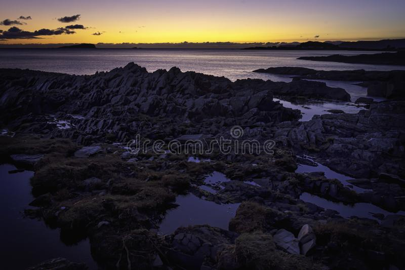 Tranquil sunset scene on rocky beach, on west coast of Scotland stock image