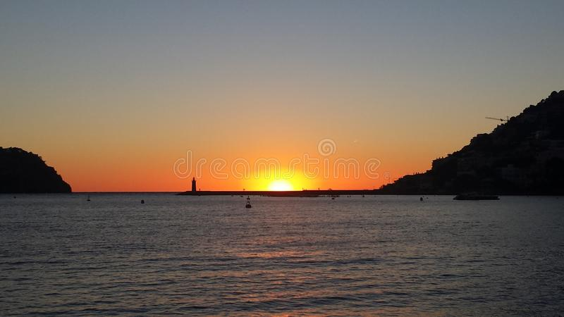Tranquil sunsets in the med. The lighthouse in Port Anratx with the sun setting behind it royalty free stock photography