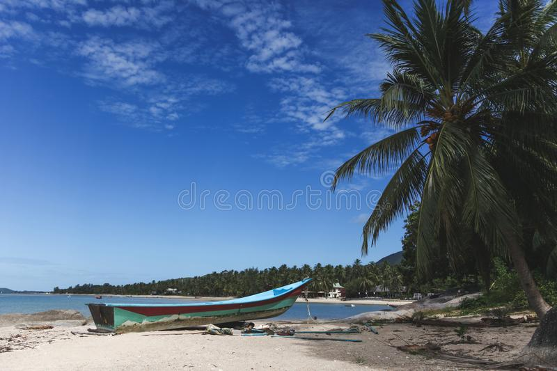 Tranquil tropical beach with old boat. On sunny day royalty free stock images