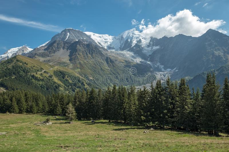 Tranquil view of Mont Blanc massif near Bellevue station, France. View of Mont Blanc massif, glaciers and forests looking across grassy fields in the foreground royalty free stock images