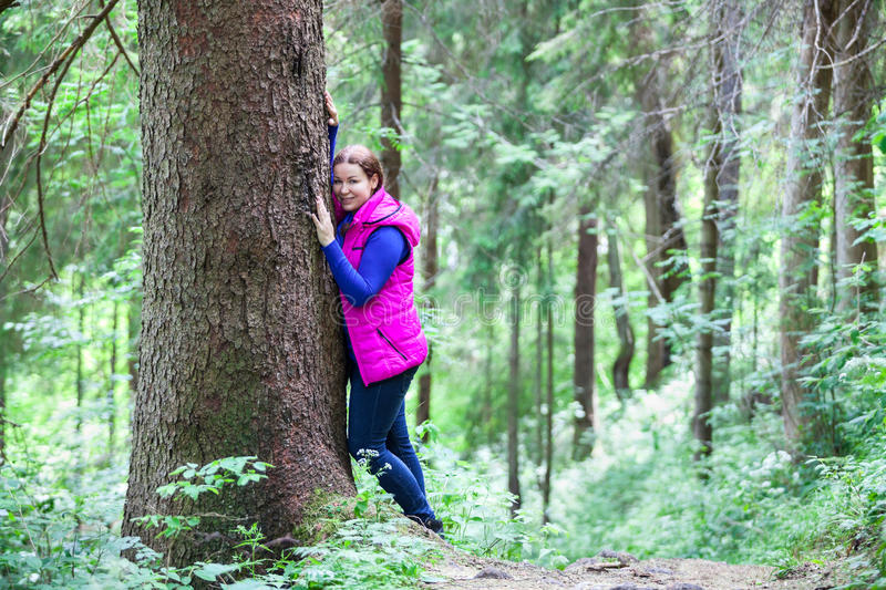 Tranquil young woman standing cheek to tree stock photography