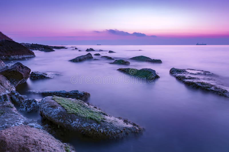Tranquility and calm. Long exposure rocky coast before sunrise stock photo