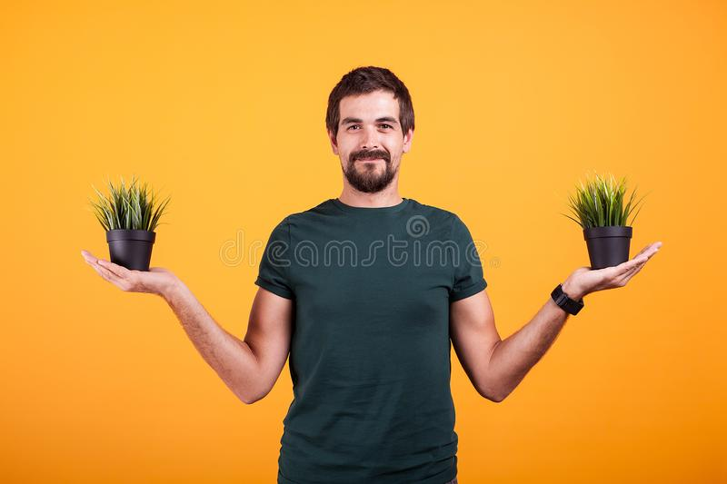 Tranquility concept image of relaxed man holding two pots of grass. In his hands royalty free stock photography