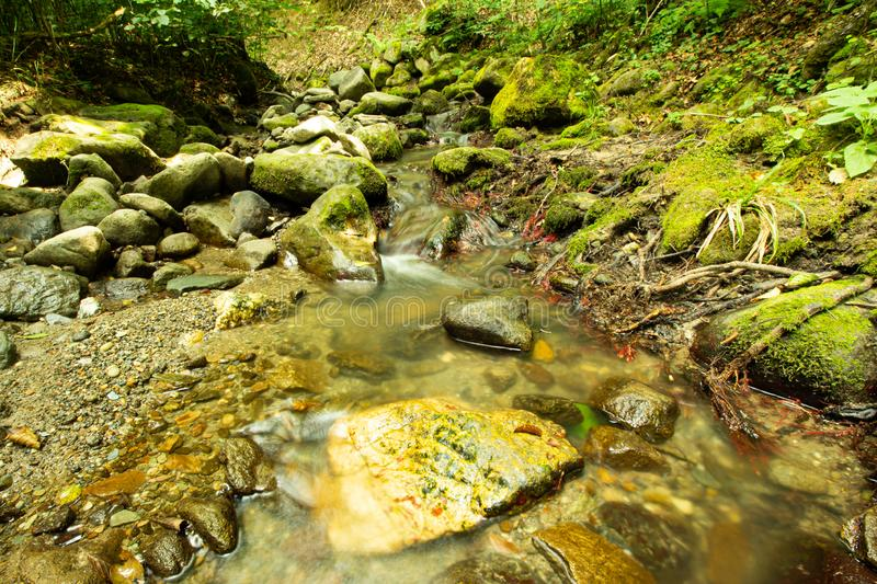 Tranquility river water in the mountain forest. Tranquility river water flowing gently and peacefully in the mountain green forest with big rocks stock photos