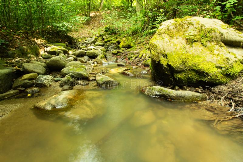 Tranquility river water in the mountain forest. Tranquility river water flowing gently and peacefully in the mountain green forest with big rocks stock photography