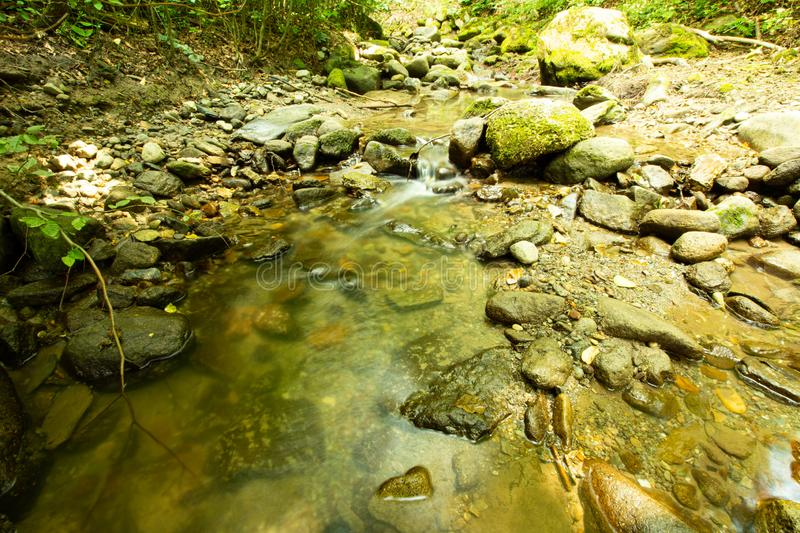 Tranquility river water in the mountain forest. Tranquility river water flowing gently and peacefully in the mountain green forest with big rocks royalty free stock images
